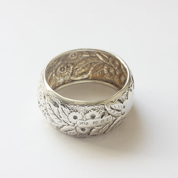 a silver victorian heavily embossed floral napkin ring dated 1898