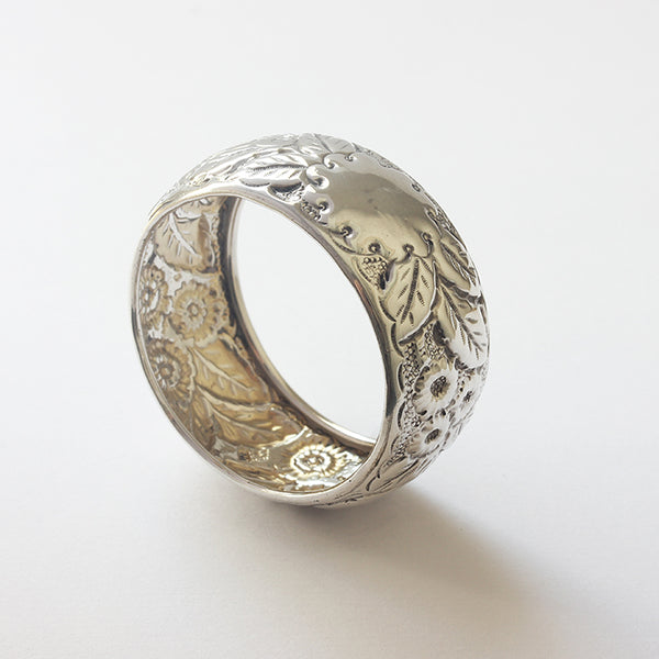 a silver napkin ring with embossed flowers and plain motif dated 1898