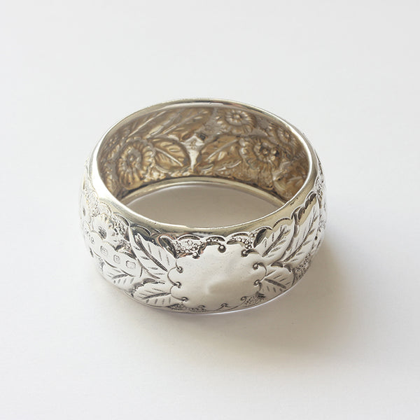 a secondhand silver serviette ring with floral pattern embossed and plain motif for engraving