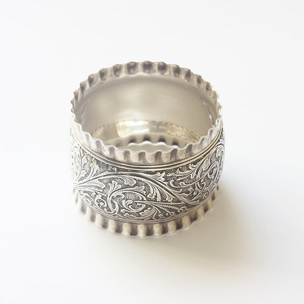 a secondhand silver serviette ring with leaf scroll pattern