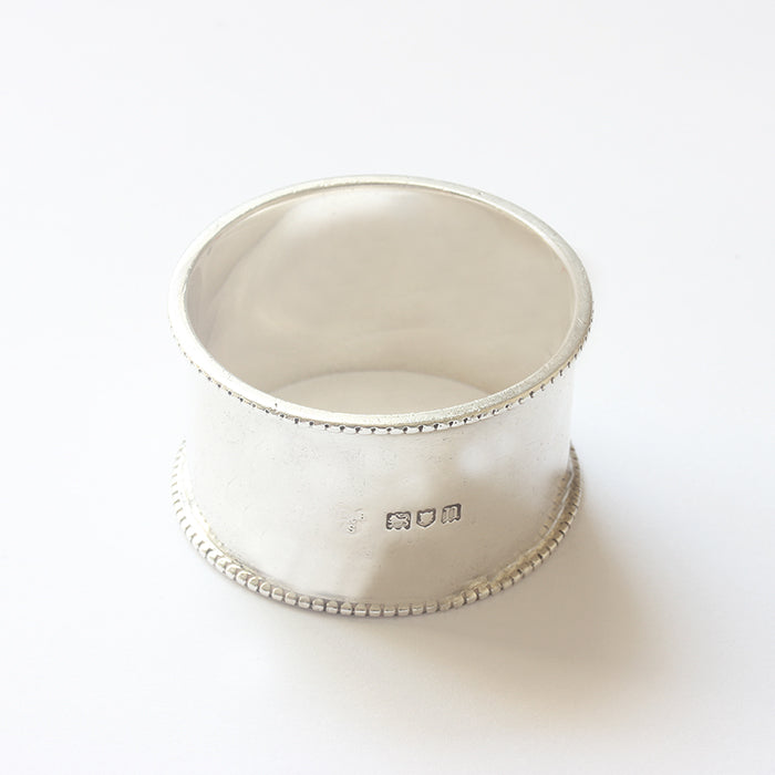 a plain antique solid silver napkin ring with bead edge and hallmark
