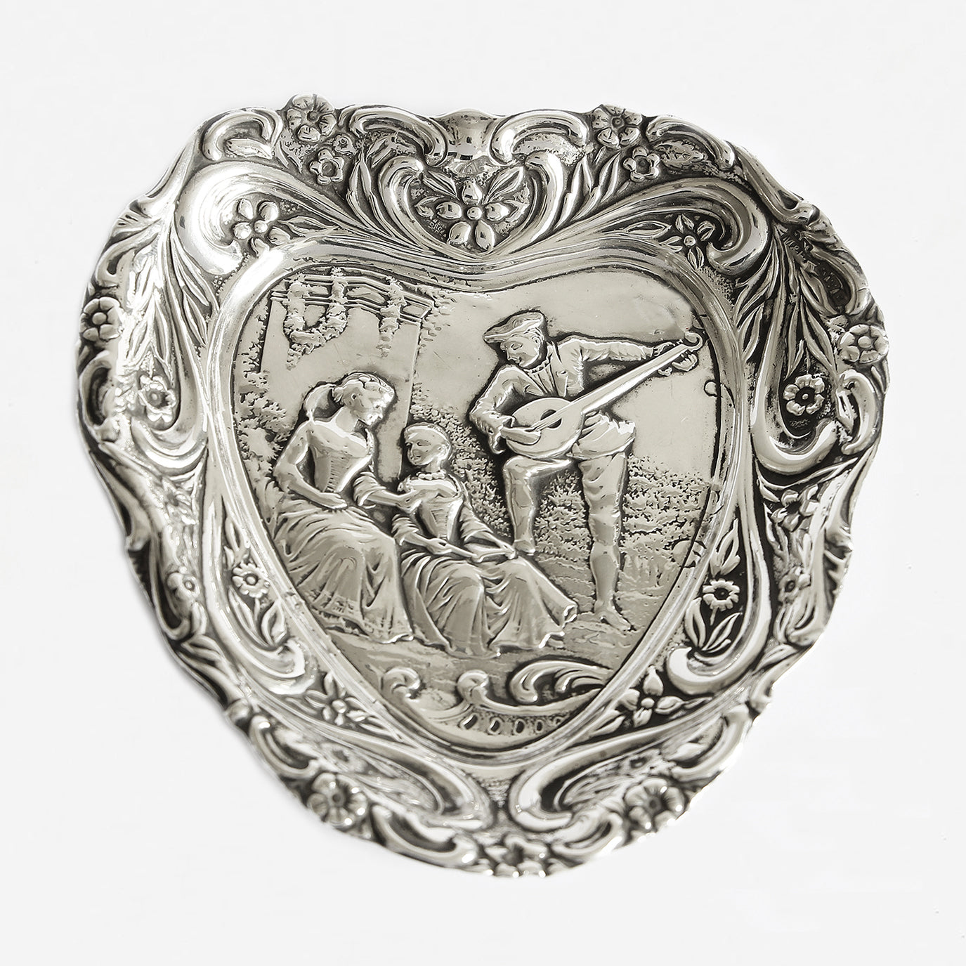 a heart shaped silver small tray with a gentleman serenading 2 ladies dated 1900