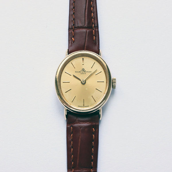 a superb ladies baume and mercier watch with gold case and leather strap