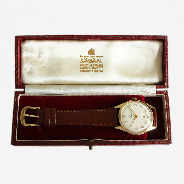 a vintage secondhand garrard watch with gold case and brown leather strap and box