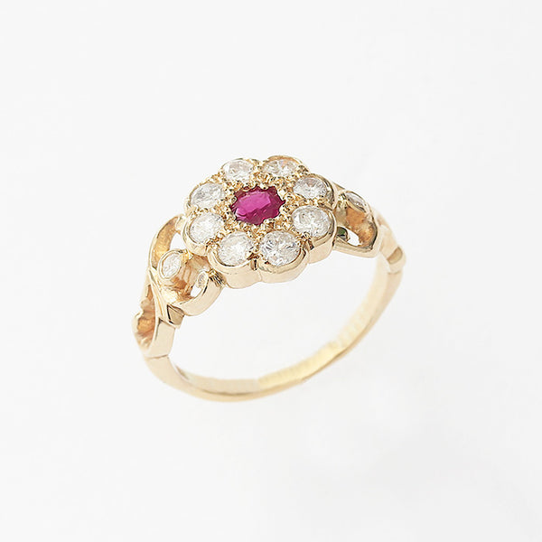 a ruby and diamond cluster in the shape of a daisy in a yellow gold setting and band