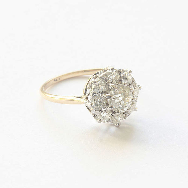a beautiful diamond cluster ring in platinum setting with yellow gold band