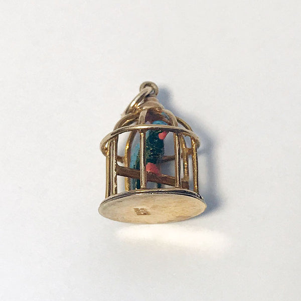 a vintage charm for a bracelet with a pink and blue enamel parrot in a cage