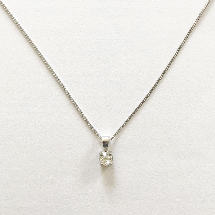 a diamond set oval faceted pendant in a 4 claw white gold pendant and curb chain