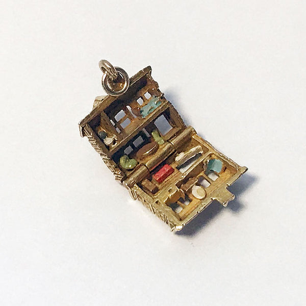 a fine quality gold vintage dolls house charm with enamel furniture
