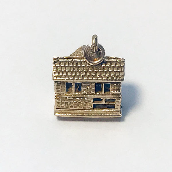 a fine gold detailed dolls house charm which opens with rooms inside