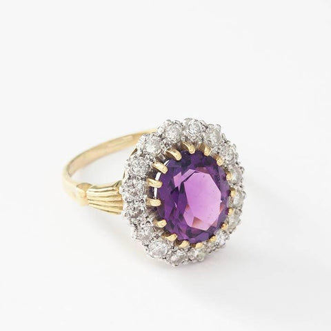 a large oval amethyst and diamond surround in a yellow gold band