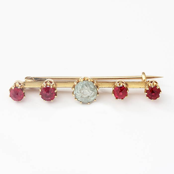 a central cushion shaped aquamarine with 4 round rubies in a line claw set on a yellow gold bar with metal pin brooch