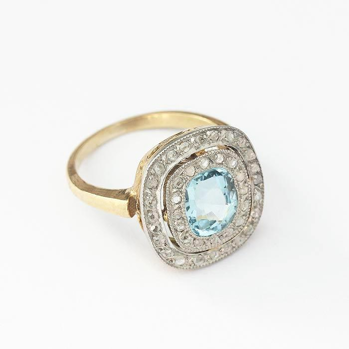 a cushion shaped aquamarine and a double surround of diamonds with a yellow gold band and millegrain settings