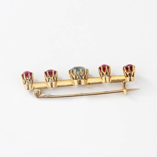 a ruby and aqua bar brooch in yellow gold with a claw setting