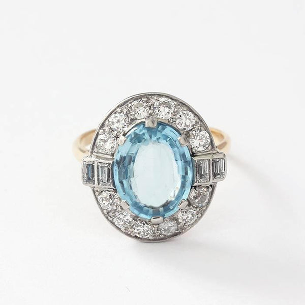 an oval aquamarine in the centre with a surround of diamonds in a white gold setting and yellow gold band