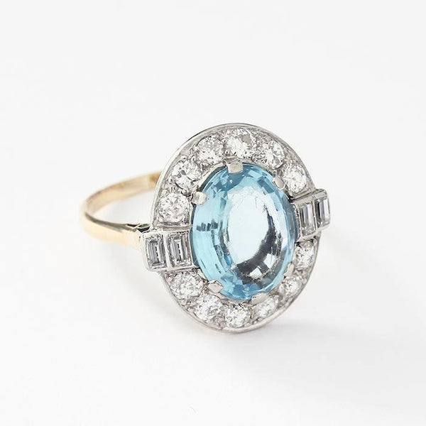 a large oval aquamarine and diamond cluster ring with baguette and brilliant cut stones in yellow and white gold