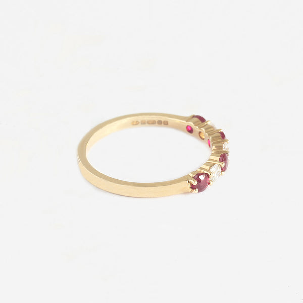 a ruby and diamond claw set eternity ring in yellow gold