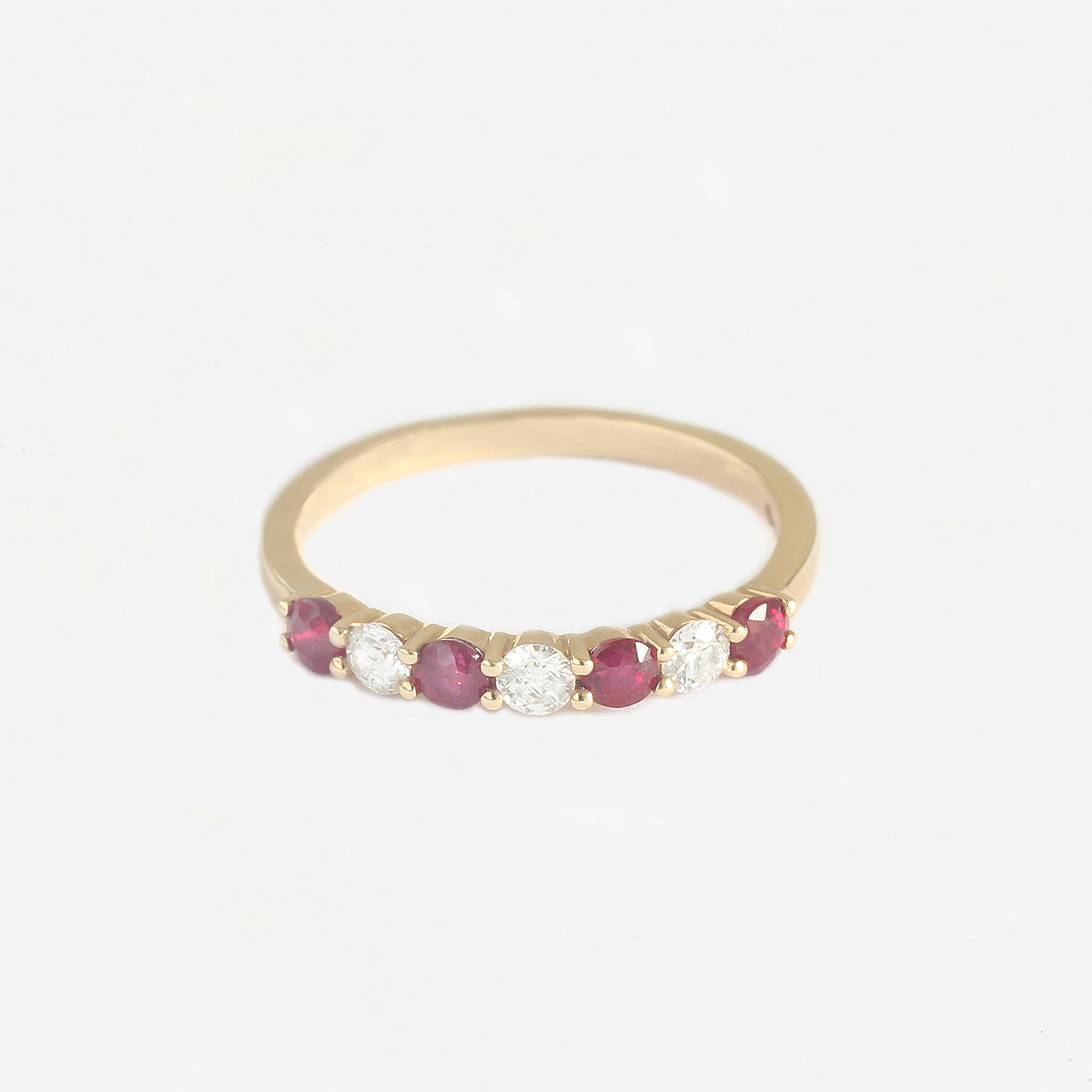 a yellow gold ruby diamond half eternity ring