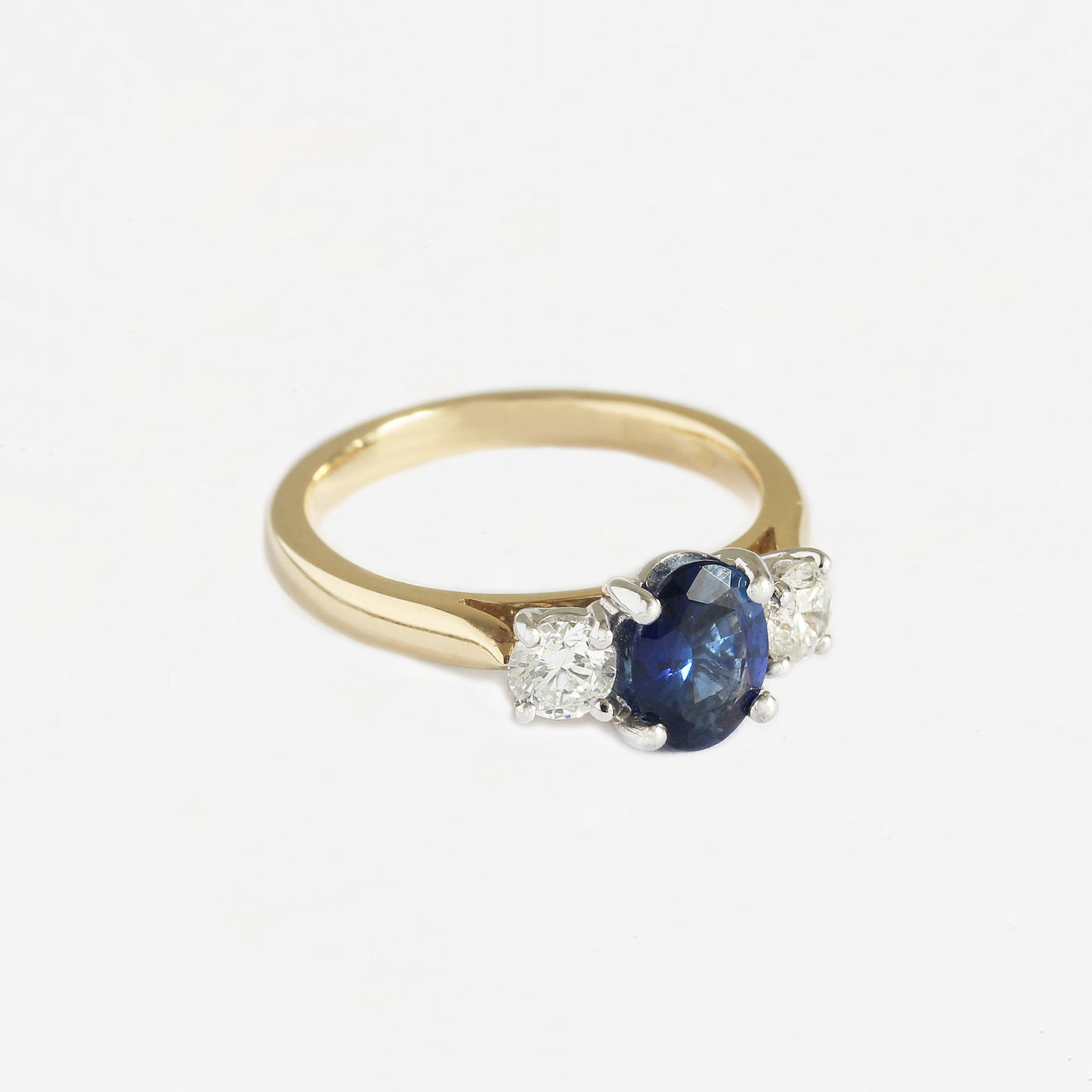 a sapphire and diamond 3 stone claw set ring in 18 carat gold