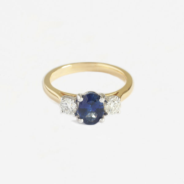 a yellow and white gold oval sapphire and diamond 3 stone claw set ring