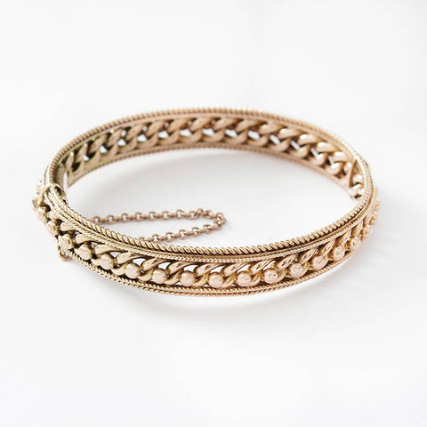 a beautiful antique bead and curb link oval gold bangle with safety chain