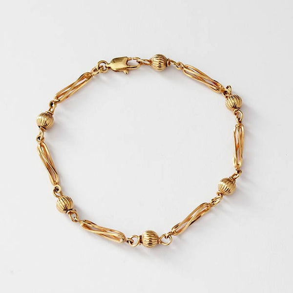 a ball and twisted design link bracelet in yellow gold with trigger clasp and hallmarked