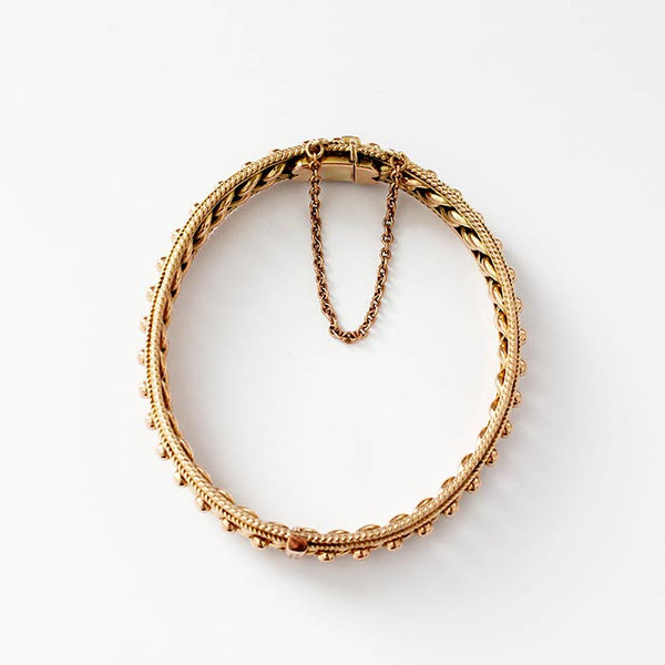 an oval antique gold bangle with a bead and curb link design and a box snap and safety chain