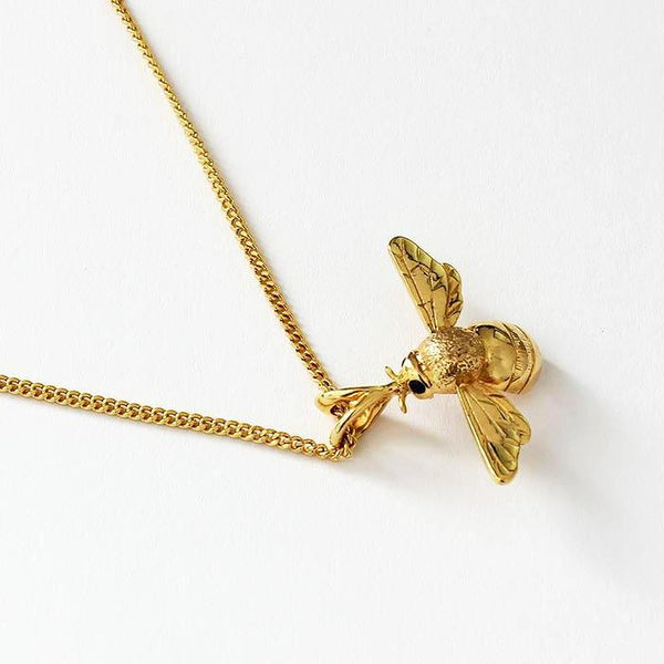 a modern yellow gold bee pendant with sapphire eyes sitting beneath a curb link yellow gold chain