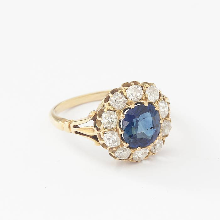 a beautiful cushion shape sapphire with a surround of 10 old cut diamonds in a yellow claw setting and plain yellow gold band