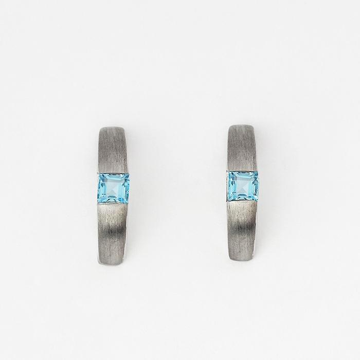 contemporary blue topaz half hoop earrings made in silver with butterfly fittings