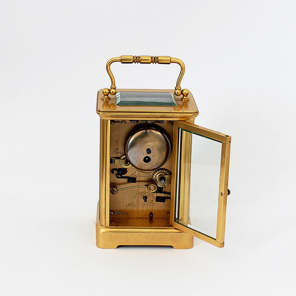 a brass carriage clock which is antique and white dial and brass case