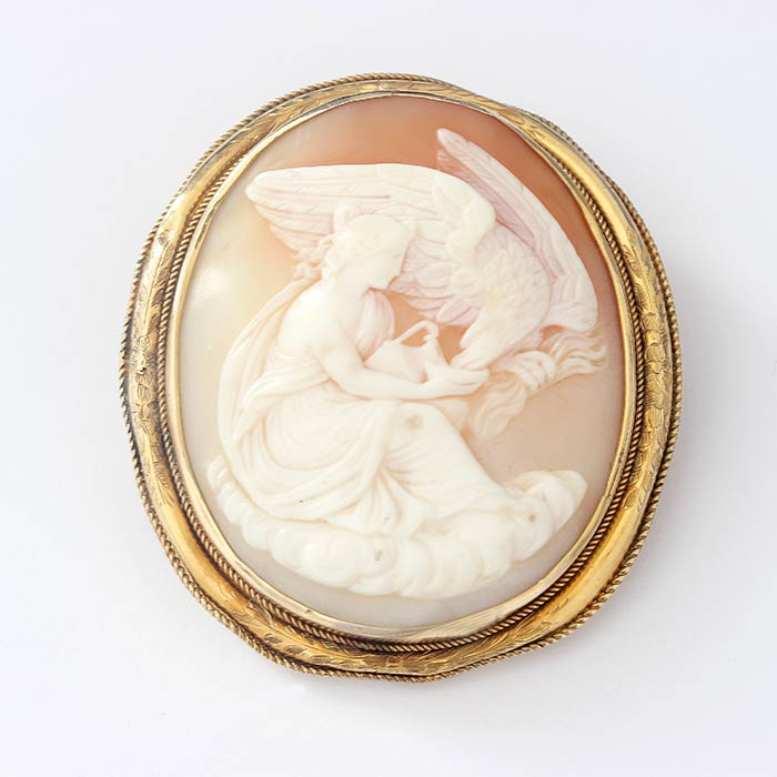 a large rounded cameo with a lady and an eagle scene with a gold 9 carat roped and leaf border