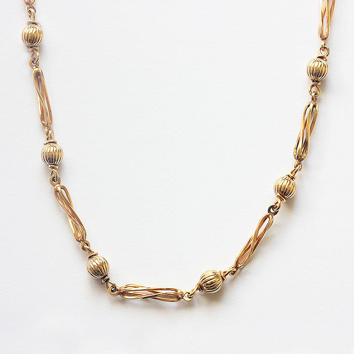 a 9 carat yellow gold cage and ball twisted design necklace