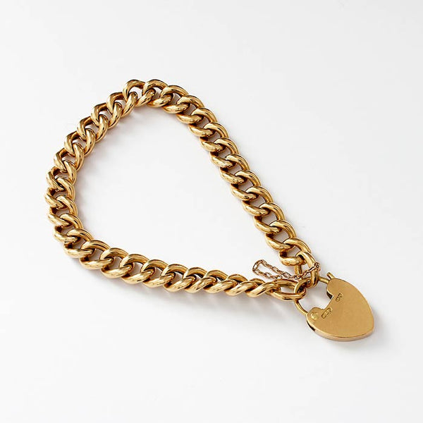 a secondhand antique yellow gold charm bracelet with curb links and a padlock clasp with safety chain
