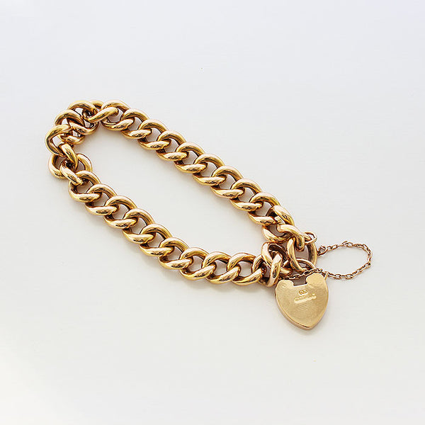 a preowned 15 carat yellow gold charm bracelet curb link with safety chain and padlock