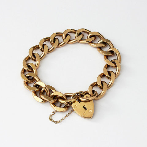a secondhand heavy solid charm bracelet in yellow gold and hallmarked