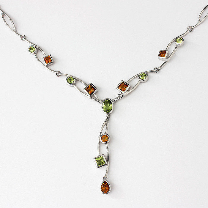 a silver citrine and peridot stone set drop necklace with rub-over setting