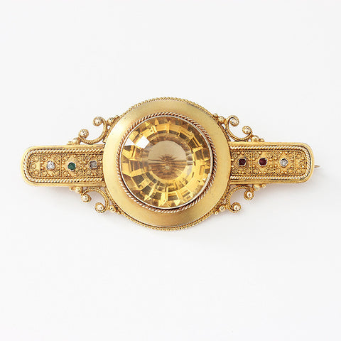 a victorian citrine brooch with fire gilt finish and small stones each side engraving on reverse