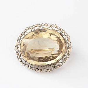 a large oval faceted light citrine brooch in a yellow gold bead and scroll border and pin