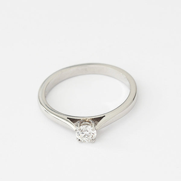 a platinum diamond engagement ring with a round stone and a claw setting