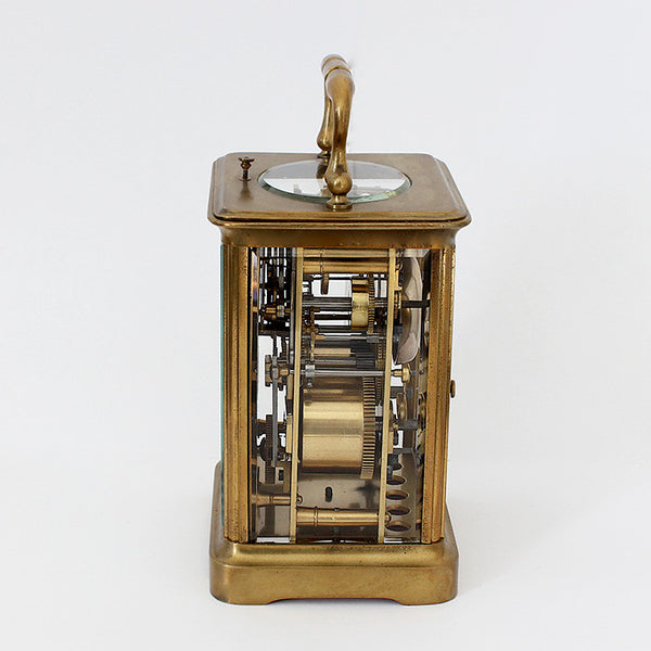 mechanical antique carriage clock with a brass case and white dial and 8 day movement