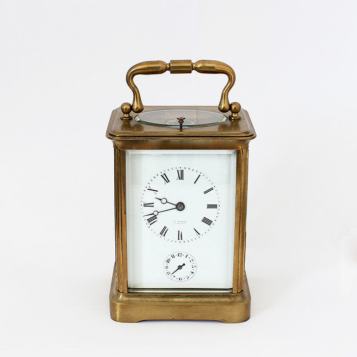 antique carriage clock with a brass case and white dial