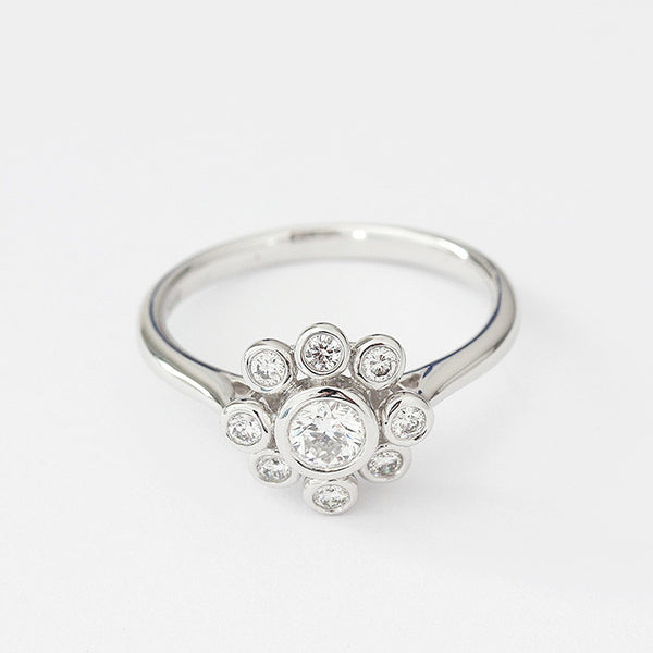 18ct white gold diamond cluster ring in a flower shape and rubover setting
