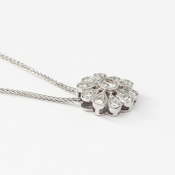 a cluster pendant with diamonds in a grain setting and a white gold chain