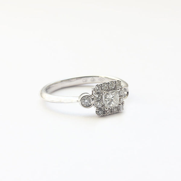 a beautiful diamond set cluster ring with brilliant and princess cut stones white gold