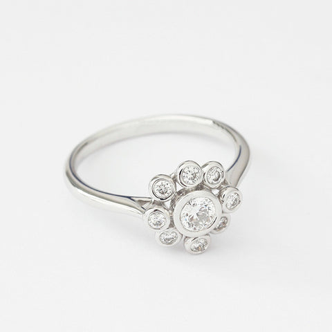 a modern diamond ring in a flower cluster design in 18ct white gold with rubover setting