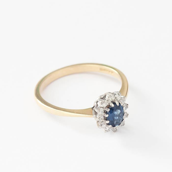 a sapphire and diamond small cluster ring in claw settings with a white and yellow gold mount