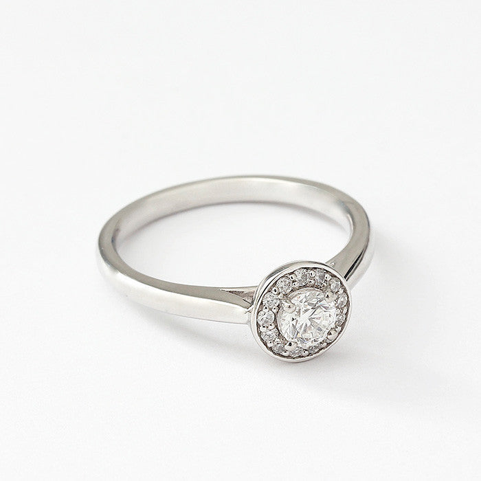 a platinum diamond cluster design ring with round stone in the centre