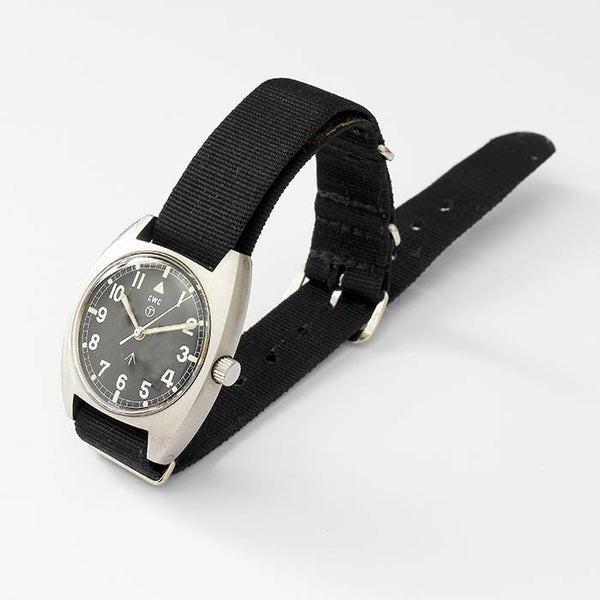 a vintage military cwc mens wrist watch with a black dial and satin case and a black fabric strap