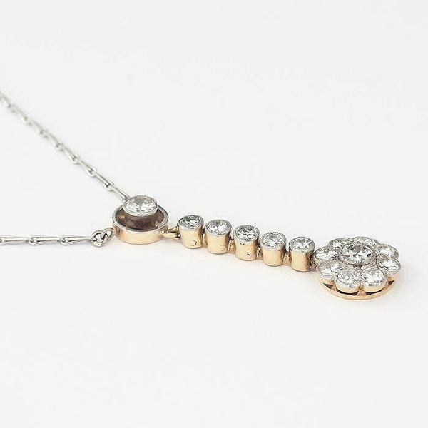 a 15 stone diamond set drop pendant with grain settings and a platinum chain
